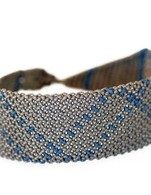 Ανδρικό βραχιόλι macrame 30mm κατασκευασμένο σε γεωμετρικό μοτίβο με πλάγιες ρίγες. Μπλε ίχνη διασταυρώνονται σχεδιασμένα πάνω σε νήμα με γκρι απόχρωση. Πλεγμένο με νήματα κηροκλωστής.