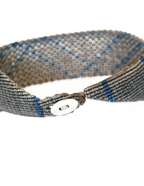 Ανδρικό βραχιόλι macrame 30mm κατασκευασμένο σε γεωμετρικό μοτίβο με πλάγιες ρίγες. Μπλε ίχνη διασταυρώνονται σχεδιασμένα πάνω με νήμα σε γκρι απόχρωση.