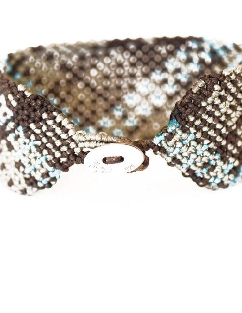 Ανδρικό βραχιόλι macrame 30mm κατασκευασμένο σε γεωμετρικό μοτίβο με πλάγιες ρίγες. Μπεζ και γαλάζια ίχνη σε αταξία διασταυρώνονται πάνω με νήμα σε καφέ βάση. Πλεγμένο με νήματα κηροκλωστής.