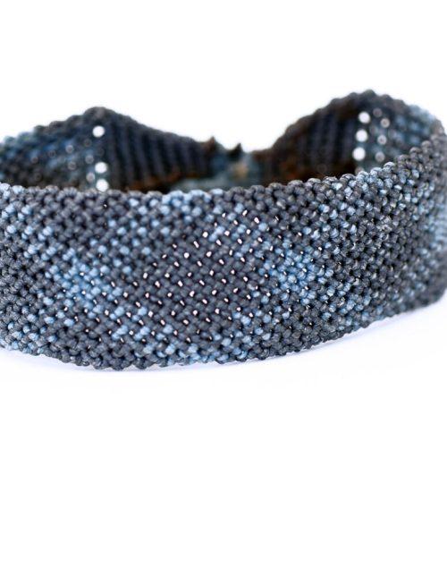 Ανδρικό βραχιόλι macrame 30mm κατασκευασμένο σε γεωμετρικό μοτίβο με πλάγιες ρίγες. Ίχνη ανοιχτού μπλε διασταυρώνονται πάνω σε νήμα με σκούρο μπλε χρώμα έτσι ώστε να σχηματιστούν επαναλαμβανόμενοι ρόμβοι. Πλεγμένο με νήματα κηροκλωστής.