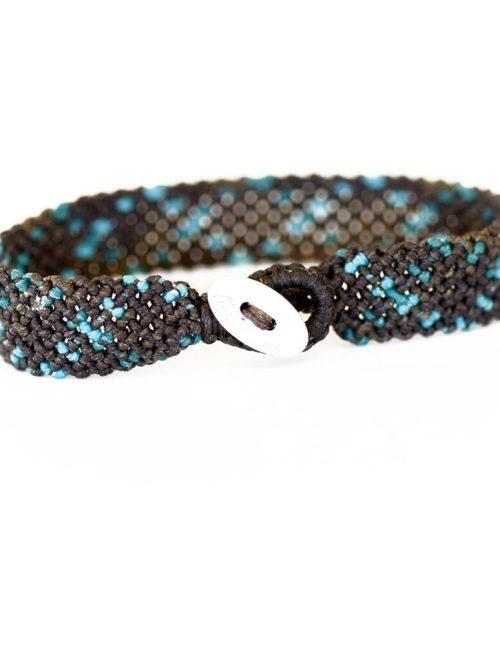 Ανδρικό βραχιόλι macrame 15mm κατασκευασμένο σε γεωμετρικό μοτίβο με πλάγιες ρίγες. Ίχνη σε μπλε απόχρωση σχεδιασμένα πάνω σε νήμα καφέ χρώματος διασταυρώνονται επαναλαμβανόμενα δημιουργώντας ρόμβους.