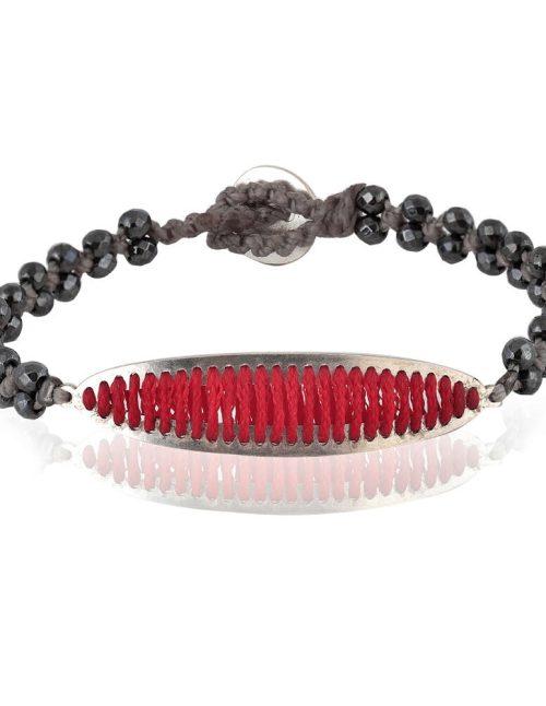 """Γυναικείο βραχιόλι που συνδυάζει την αργυροχρυσοχοΐα με το δέσιμο λίθων. Ασημένιο στοιχείο διακοσμημένο με νήμα σε κόκκινη απόχρωση πάνω σε βάση από αιματίτη ταγιέ 3mm. Ο αιματίτης βρίσκεται πλεγμένος σε ζεύγη με κηροκλωστή γκρι χρώματος. Σχέδιο από τη συλλογή """"Διελεύσεις""""."""