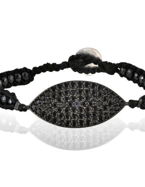 """Γυναικείο βραχιόλι διακοσμημένο με ασημένιο στοιχείο πάνω στο οποίο βρίσκονται τοποθετημένες πέτρες από μαύρο και λευκό ζιργκόν. Κάθε μία πέτρα έχει καρφωθεί στο στοιχείο με την εξειδικευμένη τεχνική στήριξης pave. Η βάση του έχει δημιουργηθεί από χάντρες αιματίτη ταγιέ 3mm σε ανθρακί απόχρωση πλεγμένες με μαύρη κηροκλωστή. Σχέδιο από τη συλλογή """"Ατέρμονα""""."""